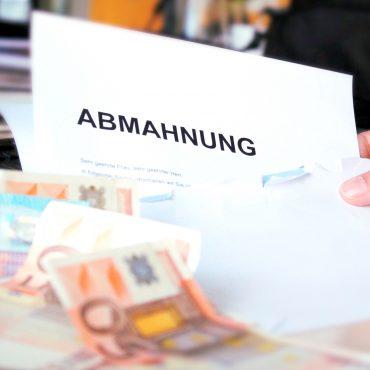 Hand hält Abmahnungsbrief, im vordergrund liegen Geldscheine