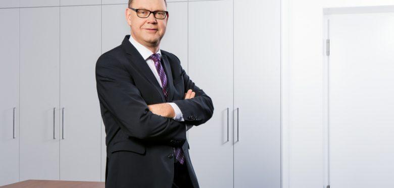 Aart De Geus, Vortsandsvorsitzender der Bertelsmann Stiftung, mit verschränkten Armen auf einem Tisch sitzend