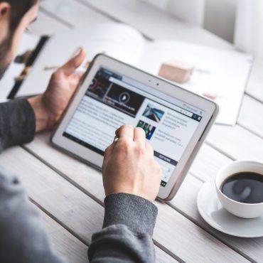 Mann hält Tablet in der Hand und sitzt an einem Tisch, Digital Leadership