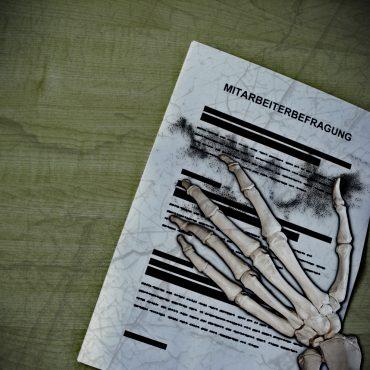 Skeletthand die auf einer Mitarbeiterbefragung liegt