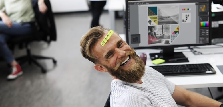 Mann mit Bart lächeln in einem kreativen Büro