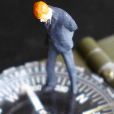 Macht im Wandel: Minitaurfigur eines Chefs auf einem Kompass