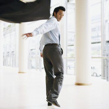 Mann im Anzug wirft im Gehen seine Anzugjacke hinter sich.
