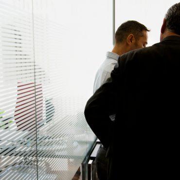 Zwei Männer stehen in einem Büro, rückwärtige Ansicht.