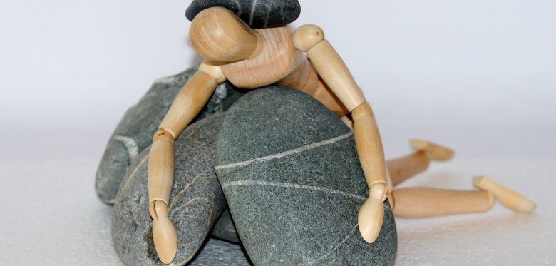 betriebliches Gesundheitsmanagement / Gliederpuppe unter Steinen begraben