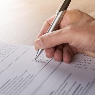 Hand hält Stift und füllt Fragebogen aus