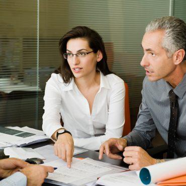 Zwei Männer und eine Frau sitzen am Schreibtisch und besprechen sich.