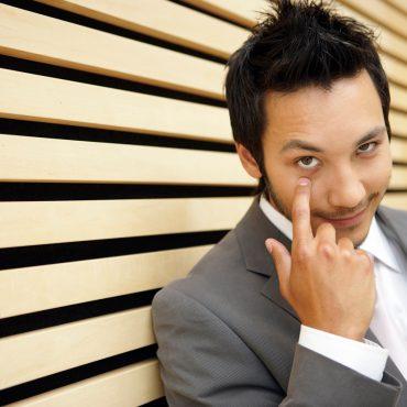 Risiko Regulierung: Mann im Anzug zeigt mit dem Finger auf sein Auge und lehnt an einer Holzwand.