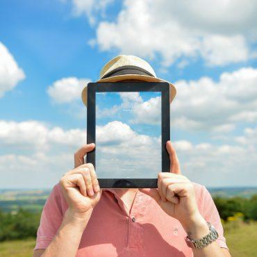 Digital Leadership - Person vor Landschaft mit einem Tablet vor dem Gesicht
