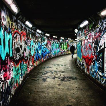 Querdenker - Person geht durch Unterführung mit Grafitti